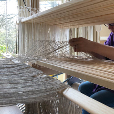 hands at work threading the heddles on a shaft loom